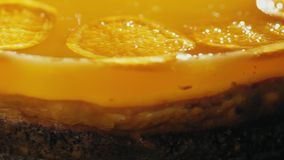 Cheesecake with tangerine jelly on top. Close-up side view: Cheesecake with tangerine jelly on top, rotates stock footage