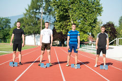 Close-up side view of cropped people ready to race on track field Royalty Free Stock Photo