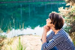 Close up Side view dreamy woman sitting on lakeside and enjoying beautiful serene day looking at lake and forest. Idyllic calm royalty free stock photo