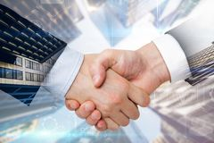 Teamwork and partnership concept. Close up and side view of handshake on blurry city background. Teamwork and partnership concept. Multiexposure royalty free stock photo