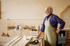 Close up side view image of tired pensive pensioner in the repair shop. Copyspace Stock Image