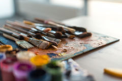 Close-up side view picture of a wooden paintbrush collection lying on old palette and gouache set in the workroom with royalty free stock photography
