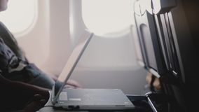Close-up side view of plane passenger watching videos on mobile tablet video player device, moving it closer to himself.