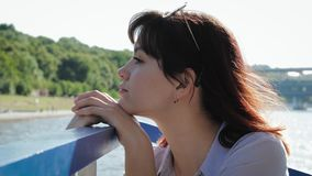 Dreamy woman put her head to railing looking from a pleasure boat on waterfront. Close up side view, portrait of dreamy young attractive woman. Put her head on stock footage