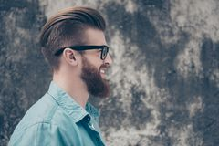 Close up side view portrait of happy smiling man in casual jeans. Clothes and black spectacles standing against concrete wall near the copy space Royalty Free Stock Image