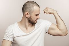 Close up side view portrait of a muscular young man showing his biceps. Sport, bodybuilding, free time, hobby, strength, power concepts. isolated on the white royalty free stock images