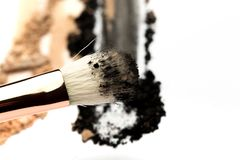 Close-up side view of professional make-up brush with natural bristle and black ferrule with crashed eyeshadow isolated on white. Background royalty free stock photo