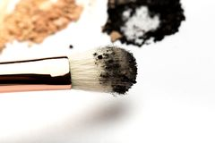 Close-up side view of professional make-up brush with natural bristle and black ferrule with crashed eyeshadow isolated on white. Background royalty free stock photography