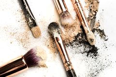Close-up side view of professional make-up brush with natural bristle and black ferrule with crashed eyeshadow on white. Background stock photo