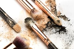 Close-up side view of professional make-up brush with natural bristle and black ferrule with crashed eyeshadow on white. Background royalty free stock image