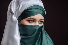Close up side view shot. a pretty lady is dressed in green hijab. Fashion moslem with pensive look Royalty Free Stock Photo