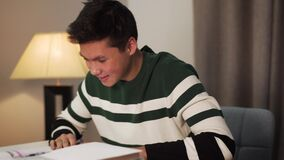 Close-up side view of smiling Asian boy writing in workbook and looking into book. Happy teenage student studying
