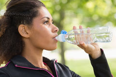Close up side view of tired woman drinking water in park Stock Photography