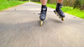 Close up side view to inline skating leg. Man easy riding on smooth way in forest park. Close up view to quick movement of inline. Boots stock video