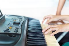 Close up side view of woman hands playing piano with hand of trainer blurry background. royalty free stock image