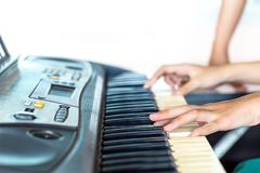 Close up side view of woman hands playing piano with hand of trainer blurry background. royalty free stock photography