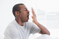 Close up side view of a young Afro man yawning Royalty Free Stock Photography