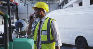 Male warehouse worker using two-way radio 4k stock video