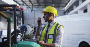 Male warehouse worker using two-way radio 4k stock footage