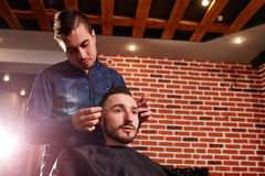 Close up side view of young bearded man getting groomed by hairdresser with comb against brick wall at barbershop. Royalty Free Stock Image