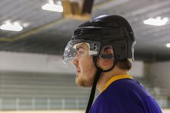 Close up side view of a young man wearing a hockey helmet. Close up side view of a young man with facial hair wearing a black hockey helmet royalty free stock image