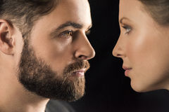 Close-up side view of young man and woman looking at each other. On black Stock Image