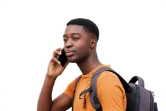 Close up side of young black man talking on cellphone against white wall. Close up side portrait of young black man talking on cellphone against white wall royalty free stock image