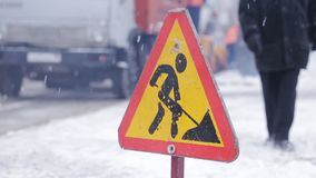 Close-up of the sign Road works, in the background the machinery removes snow from the roadside. Sign Road works is on the roadway in the winter. Cleaning of stock footage