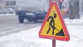 Close-up of the sign Road works, in the background the machinery removes snow from the roadside. Sign Road works is on the roadway in the winter. Cleaning of stock video footage