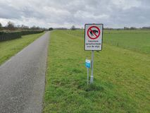 Close-up of a sign saying in Dutch dogs are not allowed to dig in this. A close-up of a sign saying in Dutch that dogs are not allowed to dig in this dike. Dog royalty free stock photo