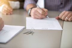 Close up of signing a loan. Close up of young people got access to home ownership signing a bank loaning, mortgage program, bound with a loan, buying a home as a stock images