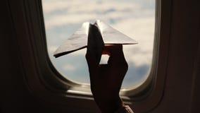 Close-up Silhouet van de hand van een kind met klein document vliegtuig tegen de achtergrond van vliegtuigvenster Kindzitting stock footage