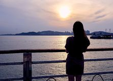 Close-up of the silhouette of an asian woman looking at the sunset view of Incheon, South Korea royalty free stock photos