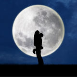 Close-up of silhouette couple hugging on full moon Stock Photos