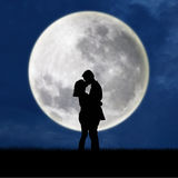 Close up of silhouette couple kissing on full moon. At night Royalty Free Stock Image