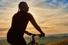 Close-up of silhouette of cyclist standing with bike against beautiful sunset. Stock Photo