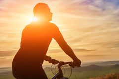 Close-up of silhouette of cyclist standing with bike against beautiful sunset. Royalty Free Stock Image