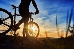 Close-up of the silhouette of young man cyclist on sunset sky with clouds. Royalty Free Stock Images