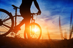 Close-up of the silhouette of young man cyclist on sunset sky with clouds. Stock Photos