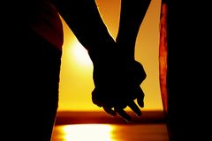 Silhouette of holding hands near sea at sunset. Close-up - silhouettes of hands holding each other against the background of sea in  sunset at the quiet sunny Royalty Free Stock Images