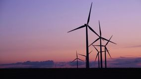 Wind turbines in the countryside under a beautiful sunset. Close-up of silhouettes of wind turbines in the countryside under a beautiful sunset stock footage