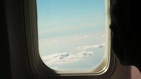 Close-up silhueta escura da menina da criança que olha para fora através do céu da visão da janela do avião e as nuvens e a paisa video estoque