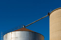 Close-up of silos on Blue Sky 2. A close up of the top of large silos on a blue sky Royalty Free Stock Photo