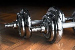 Close up silver dumbbell on floor room Stock Photography