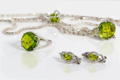 Close-up silver earrings, ring and pendant with peridot on background chain and ring on white acrylic desk. Stock Photo