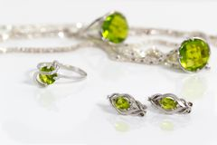 Close-up silver earrings and small ring with peridot on background pendant, chain and big ring on white acrylic desk. Royalty Free Stock Photography