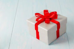 Close up of silver gift box with red ribbon. Bow on blue wooden background Stock Images