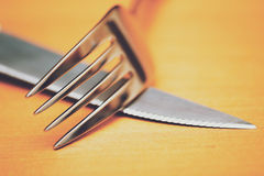 Close up of a silver knife and fork on a brown table Stock Photography