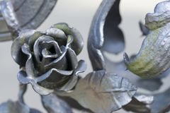 Close up on a silver metal rose, part of a metal fence. Craftmanship taken in Dresden, Germany Royalty Free Stock Image