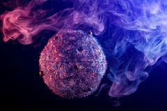 Close up of a silver shiny decoration Christmas balls. In colored purple-blue smoke, on an isolated black background. Concept of a modern Christmas card. Happy stock photo
